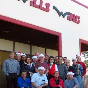 The Wills Wing Crew, 2002: Back row, standing, l-r:Ken Howells, Ruben Frausto, Victor Sosa, Eva Hanska, Peter Swanson, Mike Meier, Gary Smith, Rich Collins, Linda Meier, Paul Diehl, Martin Maldonado, Tom Blaty, Martha Diorio, Steven Pearson, Rick Zimbelman. Front row, seated, l-r: Carlos Mendosa, Chris Wills, Rob Kells, Gene Atkins, (not pictured: Mitch McAleer).
